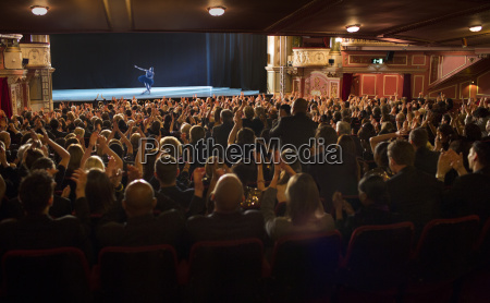 audience applauding ballerina on stage in