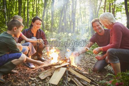 multi generation family roasting marshmallows at
