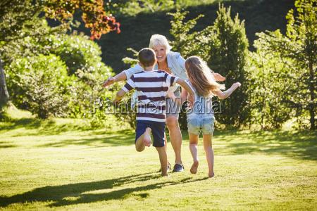 grandchildren running to grandmother in sunny
