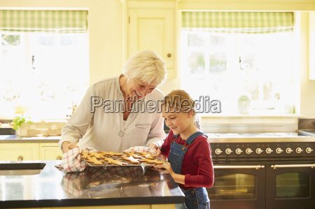 grandmother and granddaughter baking gingerbread cookies