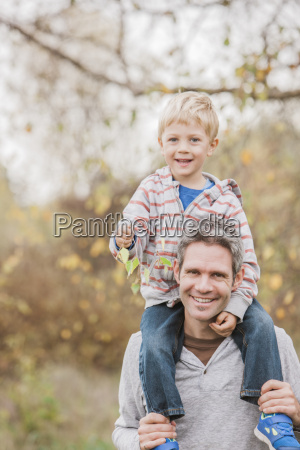 portrait smiling father carrying toddler son