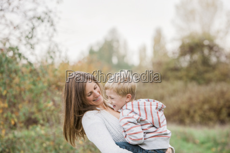 mother and toddler son laughing in