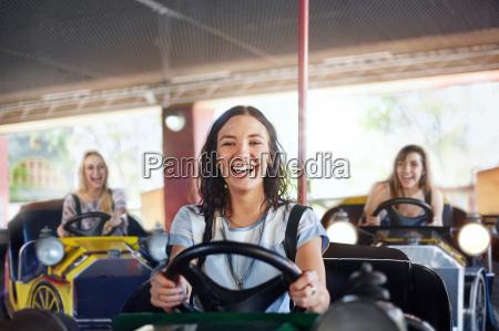 portrait smiling young woman riding bumper