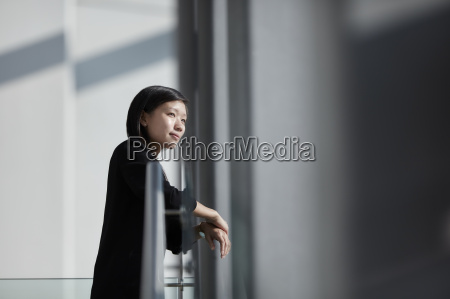pensive businesswoman looking through sunny office