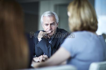 serious senior businessman looking down in