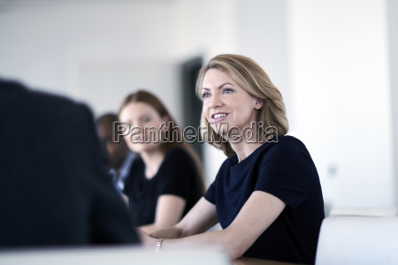 smiling businesswoman listening in meeting