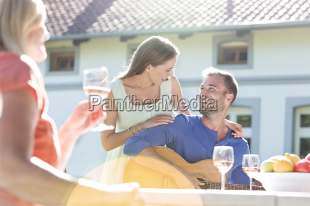smiling young couple playing guitar and