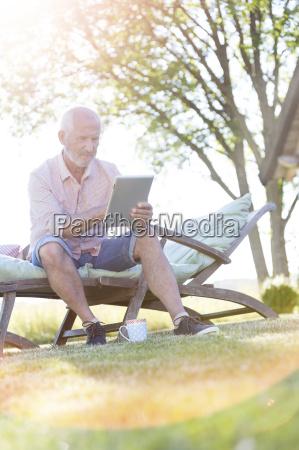 senior man using digital tablet on