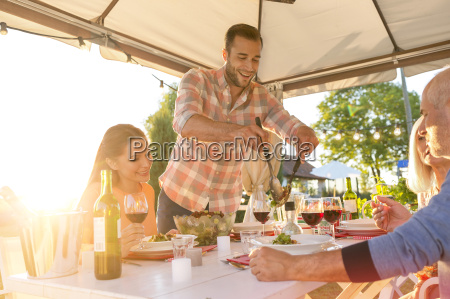 man serving salad at sunny patio