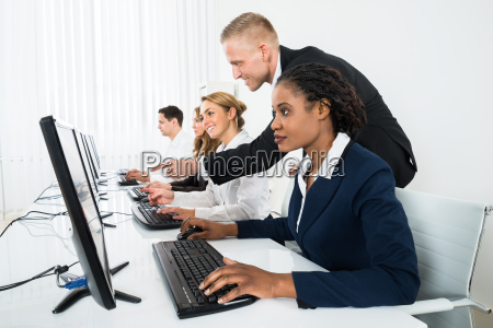 manager assisting his staff in office