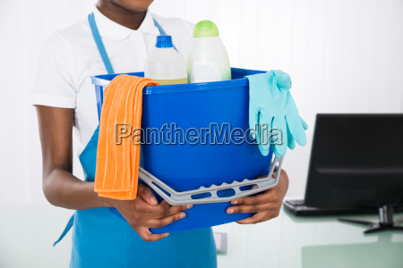 janitor holding cleaning equipments