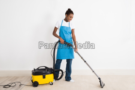 female janitor using vacuum cleaner on