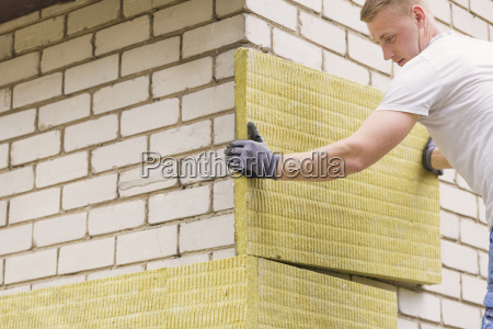 construction worker insulating house facade with