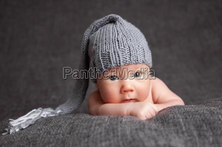 beautiful newborn wearing a cute grey