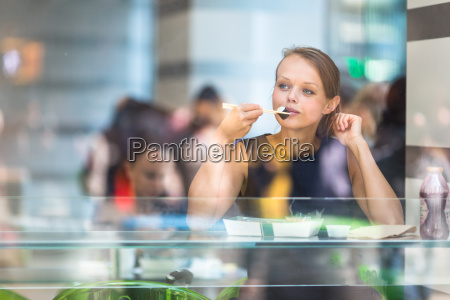 pretty young woman eating sushi in