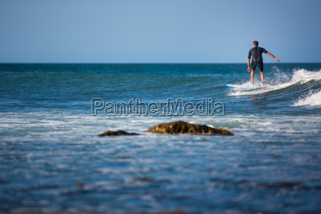 young boy surfing the wave in