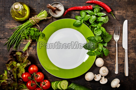 plate surrounded by fresh herbs and