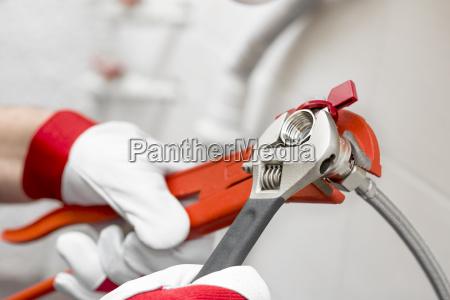 plumber screwing plumbing fittings in bathroom