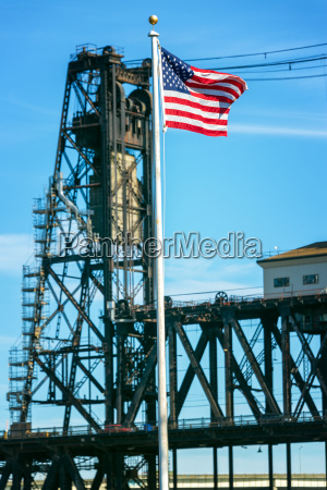american flag and steel bridge