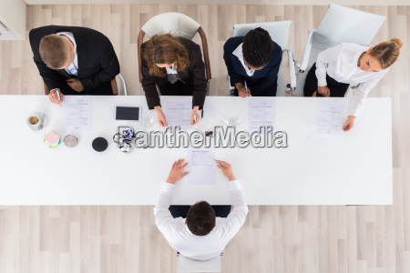 businesspeople interviewing young male applicant