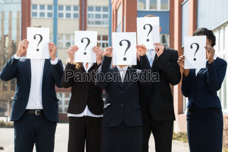 businesspeople hiding face behind question mark