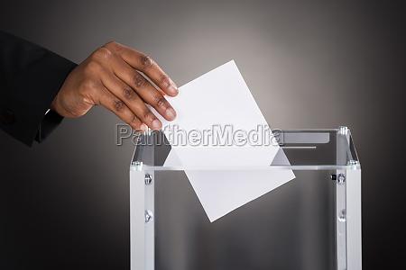 businessperson hand inserting ballot in box