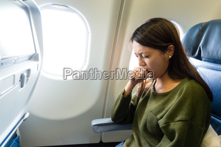 woman feeling sick inside air plane