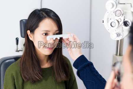 woman checking vision with tonometer at