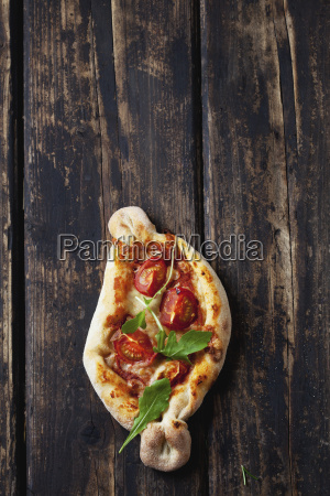 small pizza with rocket and cherry