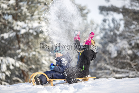two children sitting on a sledge