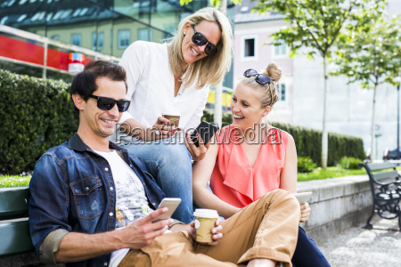happy friends on bench looking at