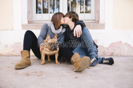 young couple with french bulldog sitting