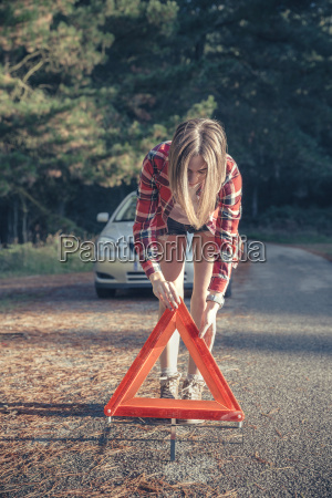 young woman putting warning triangle on