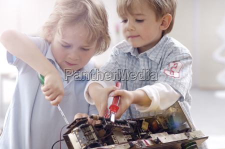 two little boys disassembling an old