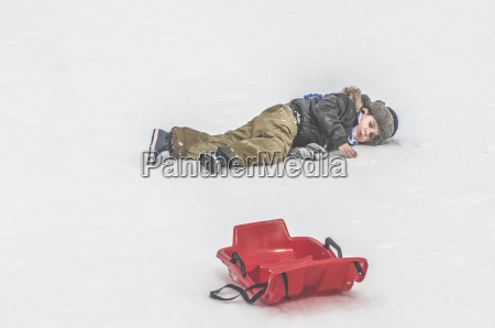 boy lying in snow next to