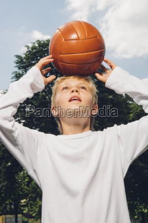 boy balancing a volley ball on