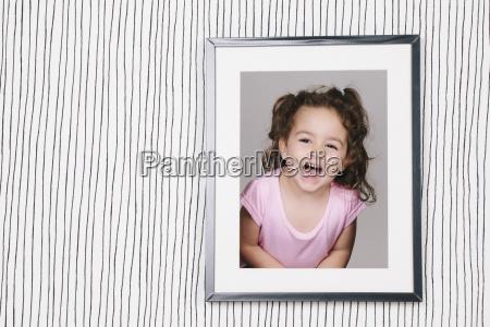 framed photography of little girl hanging