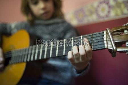 boy playing spanish guitar