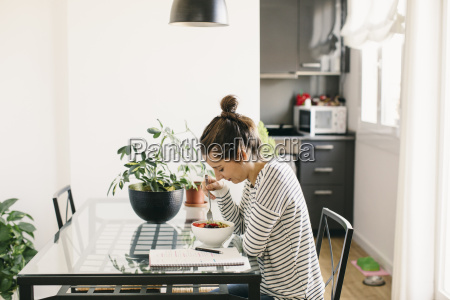 woman sitting at table with fruit