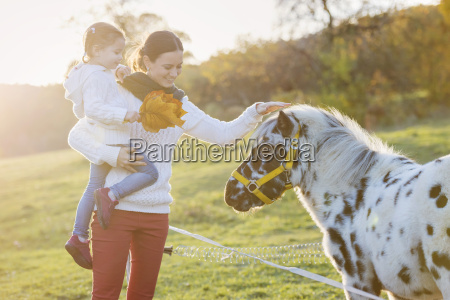 mother with daughter petting pony on