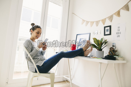 woman at home laying feet on