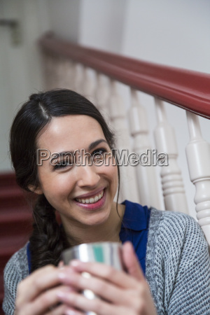 portrait of smiling woman in staircase