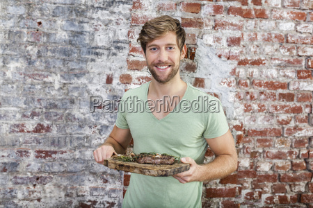 portrait of smiling man holding board