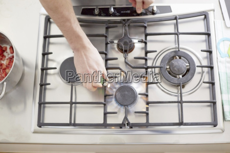 man lighting gas stove