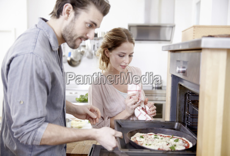 couple putting pizza into oven