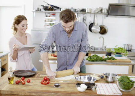 couple, preparing, pizza, dough, in, kitchen - 17387624