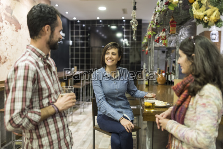 three friends socializing in a bar
