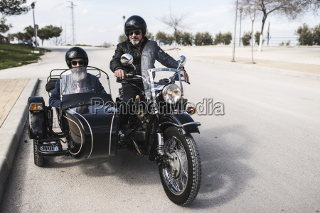two bikers standing on a road
