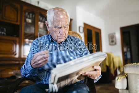senior man reading newspaper at home