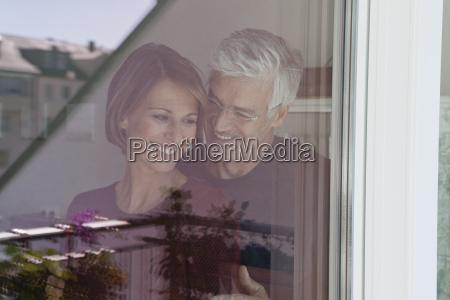 smiling couple behind window pane